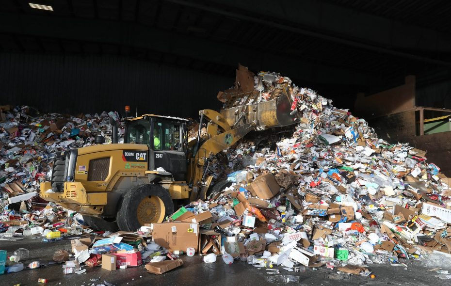 Peter Kyaw, operating a front-end loader, makes room for more materials coming in on the tipping floor at Buffalo Recycling Enterprise in South Buffalo. (Sharon Cantillon/Buffalo News)