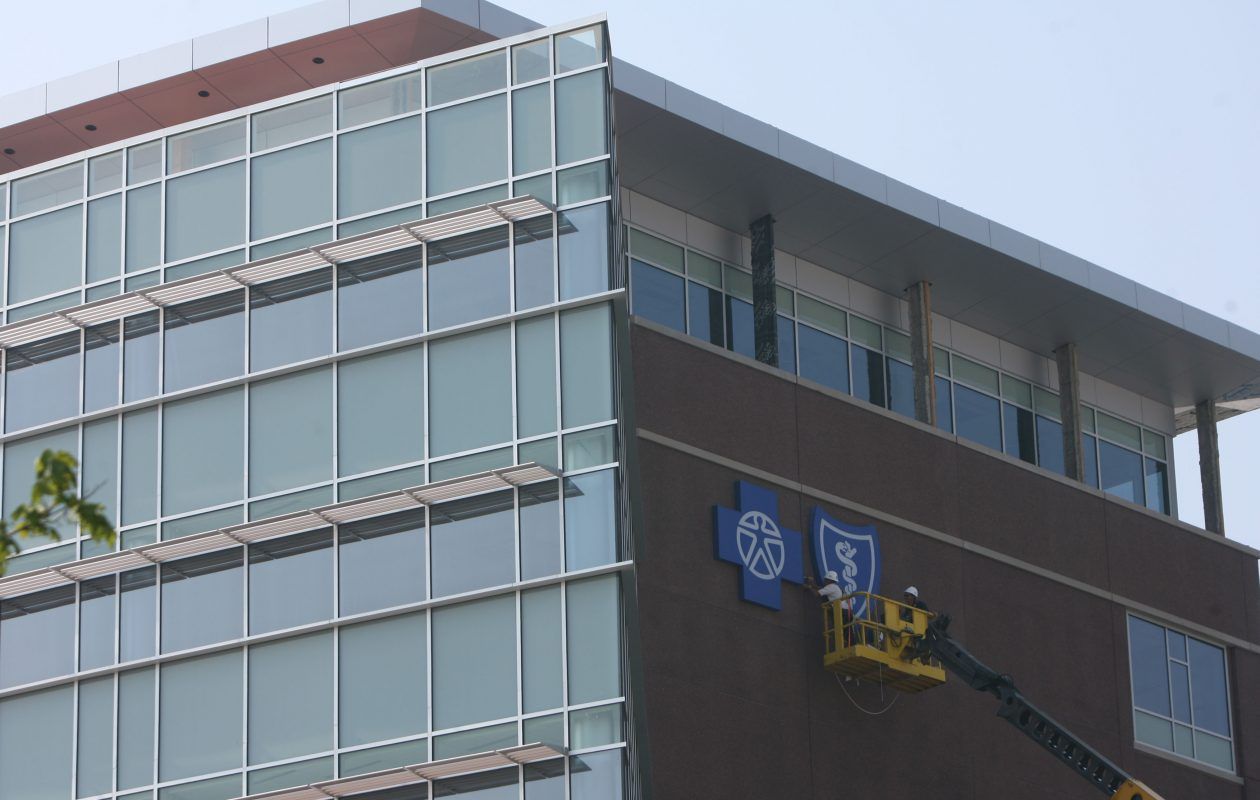 Workers install the BlueCross BlueShield logo on the outside of the new building in 2007. (News file photo)