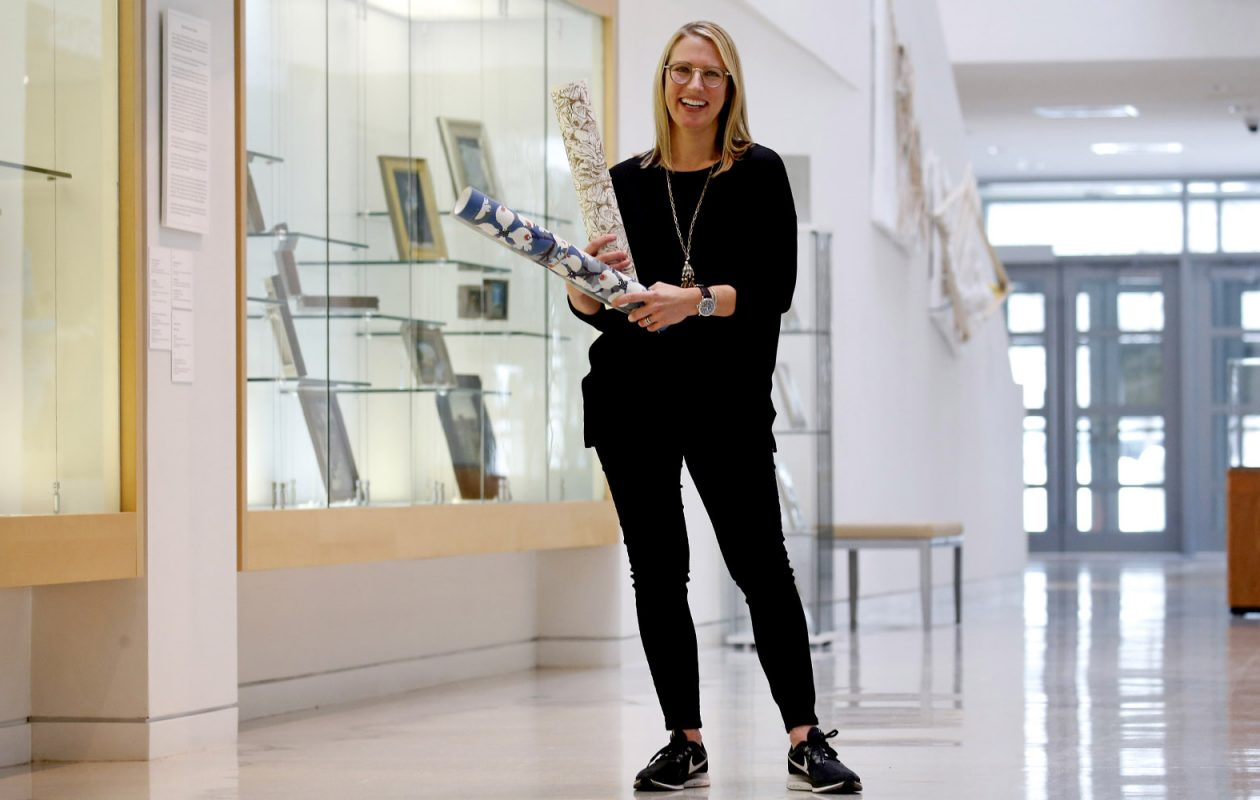 Traci Ackerman, founder of Red Disk, in the atrium of the Burchfield Penney Art Center holding a couple  wallpaper samples from Red Disk. (Robert Kirkham/Buffalo News)