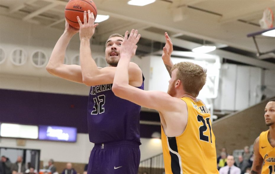Niagara forward Dominic Robb (32) scores against Canisius forward Scott Hitchon in the first half of the Purple Eagles' 78-70 win on Jan. 30 in Lewiston. (James P. McCoy/Buffalo News)
