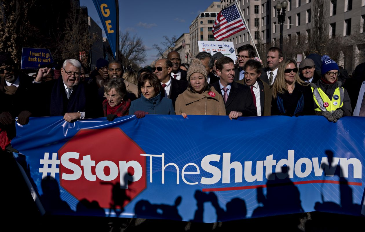 Demonstrators hold a '#Stoptheshutdown' sign Friday during a rally with union members and federal employees to end the partial government shutdown outside AFL-CIO headquarters in Washington. (Bloomberg photo by Andrew Harrer.)