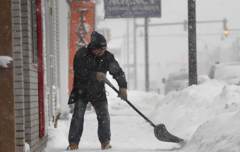 George Bechakas shovels the snow in front of his restaurant on Clinton Street in Buffalo this week. (Mark Mulville/Buffalo News)