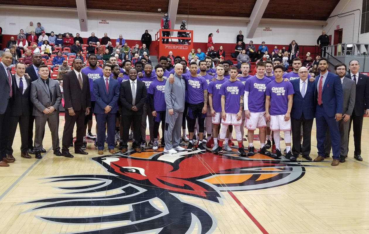 Marc Rybczyk is surrounded by Niagara players and staff as part of a Coaches vs. Cancer event at Fairfield .(Niagara Athletics)