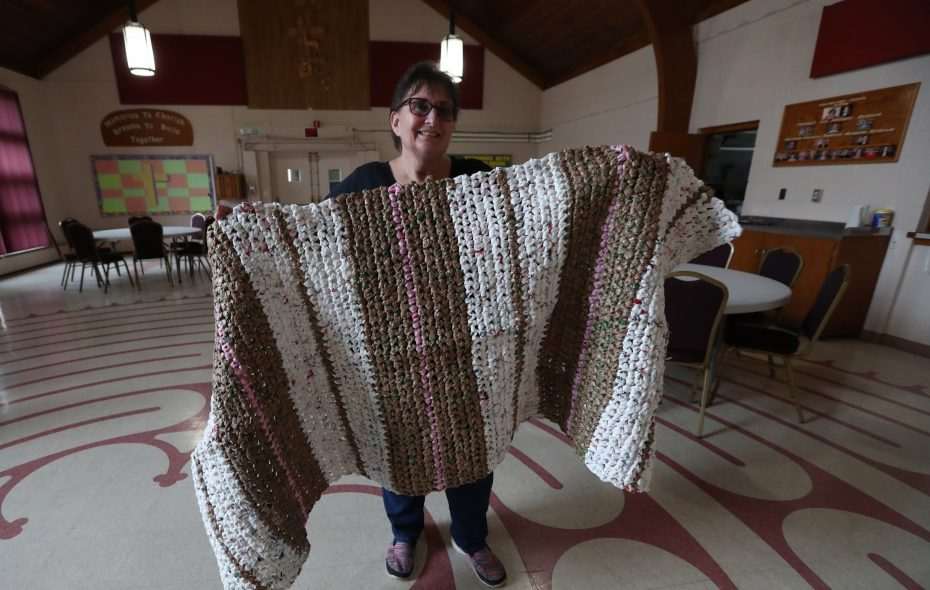 Gail Potter, founder and president of Mats for a Mission, shows off one of the mats made by a volunteer from recycled, clean plastic grocery bags.  (Sharon Cantillon/Buffalo News)