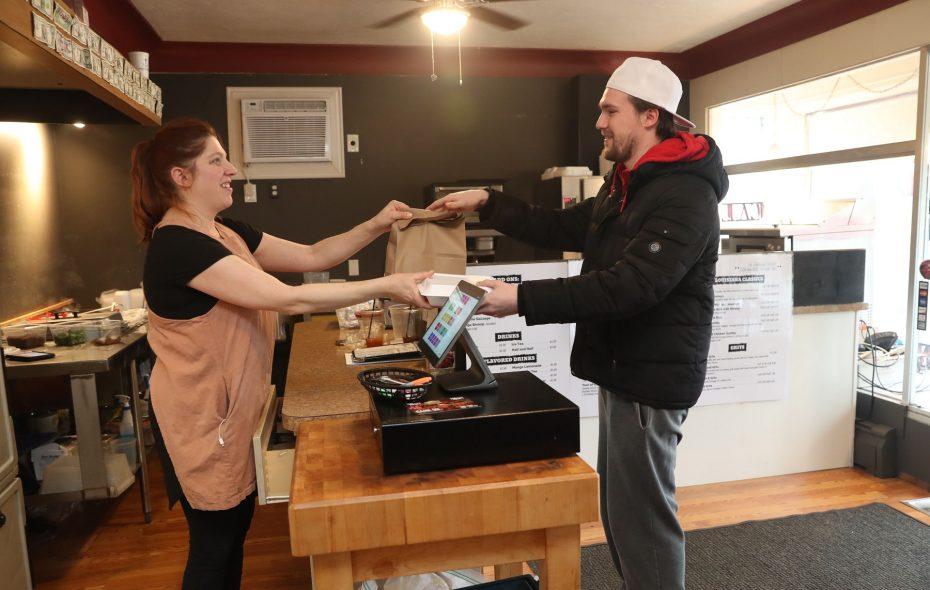 The Louisiana Cookery owner Amy Powlenko serves customer Zachary Skiva. (Sharon Cantillon/Buffalo News)