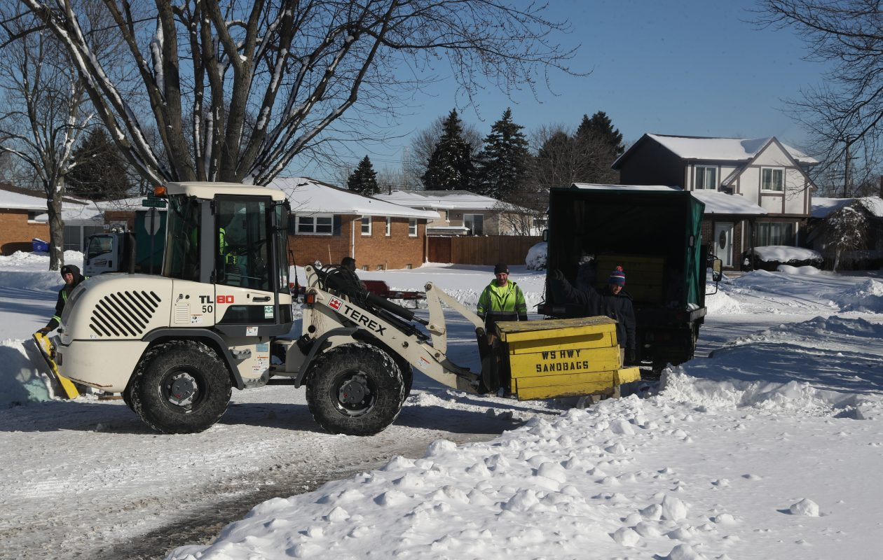 West Seneca Highway Department crews clear snow and put out sandbags, to help prevent flooding in West Seneca. (John Hickey/Buffalo News)