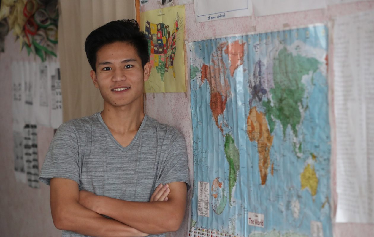 Ehkalue Soe, a 21-year-old Karen refugee from Burma, stands next to a world map in his Buffalo home. He will become a U.S. citizen during naturalization ceremonies Thursday. His mother became a citizen last October and his older brother and sister will be taking their citizenship exams in the next two weeks. (Sharon Cantillon/Buffalo News)