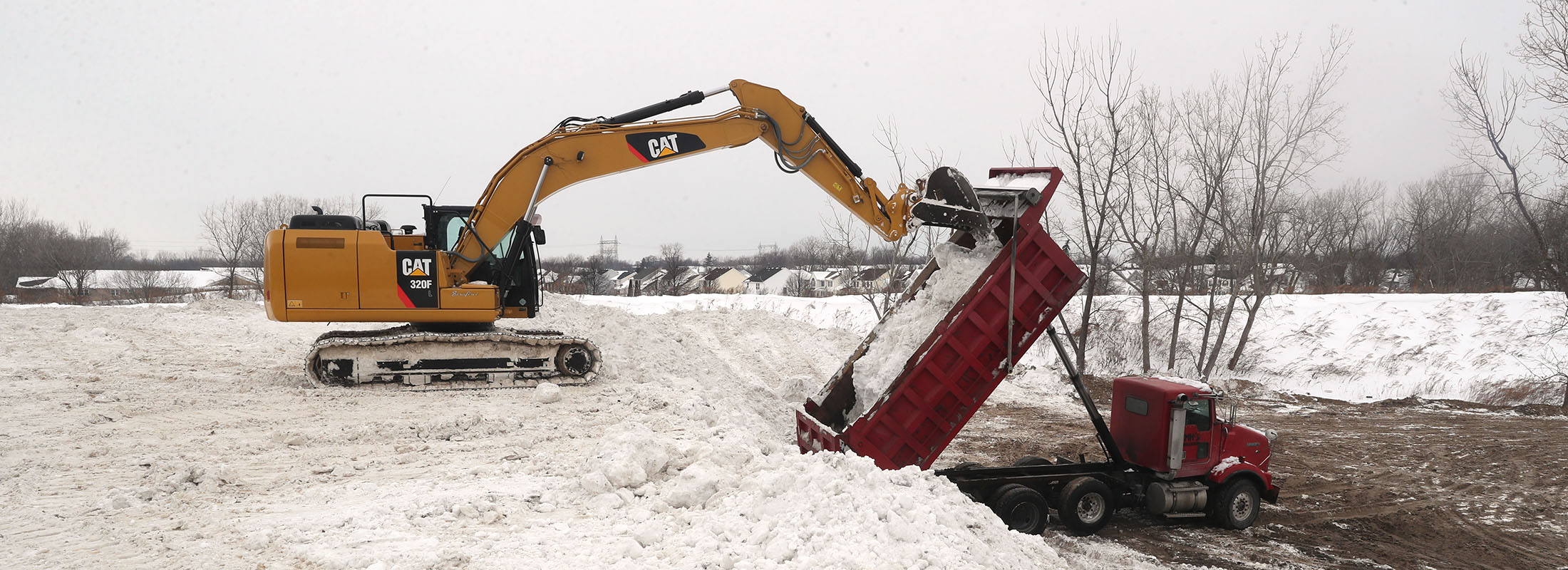 Heavy equipment moves mountains of snow from the streets of Cheektowaga to a site off Walden Avenue by Pine Ridge Road on Feb. 2.(John Hickey/Buffalo News)