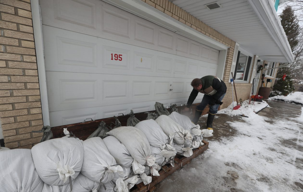 Michael Machnica uses sandbags to keep flood waters from getting into his mother's home on Lexington Green in West Seneca, to stop potential flooding on Saturday, Feb. 2, 2019. (John Hickey/Buffalo News)