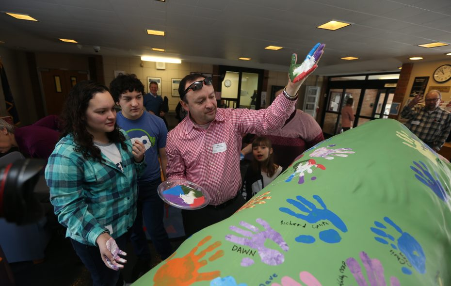 Natalia De la Espriella and her brother Nocolas watch as their father Sergio puts his handprint on a buffalo  in the Children's Psychiatric Center to celebrate the state's $30 million investment in the facility. (John Hickey/Buffalo News)