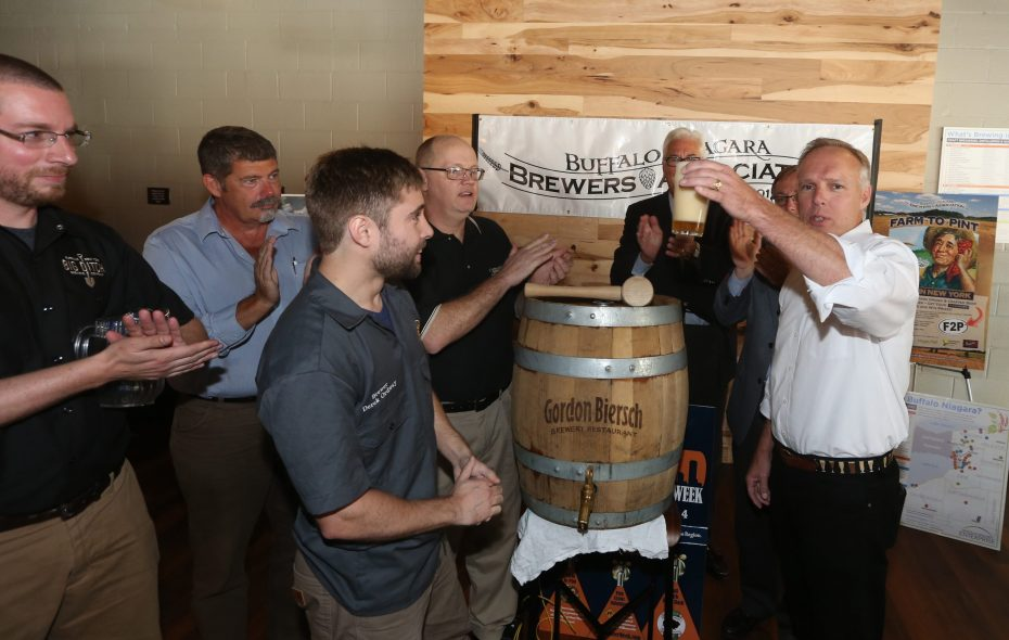 Neil Kavanaugh, right, president of Consumer's Beverages, joins, from left, Matt Kahn of Big Ditch Brewing  Steve Gill, Derek Ordway, Head Brewer Gordon Biersch, Willard Brooks, partially blocked Jack Quinn, and Sam Hoyt, at a keg tapping ceremony at Big Ditch Brewery kicking off the 6th Annual Buffalo Beer Week, on Tuesday,  Sept. 22, 2015. (John Hickey/Buffalo News)