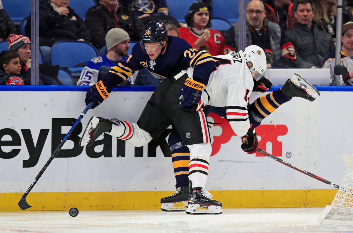 Buffalo Sabres defenseman Lawrence Pilut is pinned against the boards Friday night. (Harry Scull Jr./Buffalo News)
