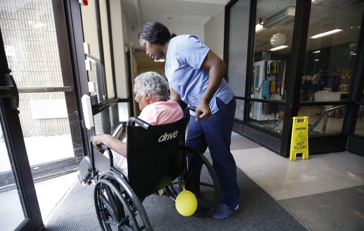 A resident of Ellicott Center for Rehabilitation and Nursing in Buffalo, gets help from staff through a doorway. The nursing home in 2017 charged $495 a day for residents paying their own way or with long-term care insurance, according to the state Department of Health. (Derek Gee/News file photo)