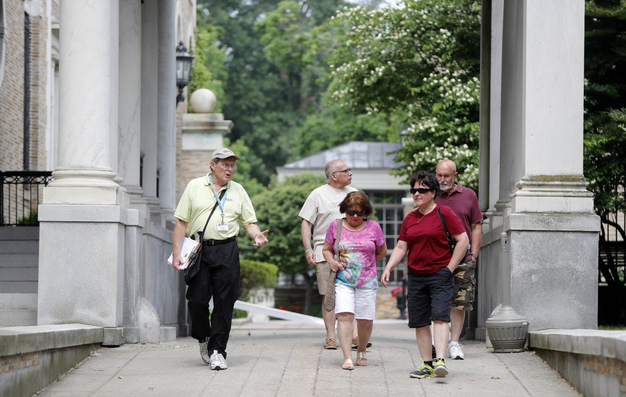 Harry Meyer, left, a volunteer docent, gives an Explore Buffalo tour of the mansions along Delaware Avenue last June in Buffalo. (Mark Mulville/News file photo)