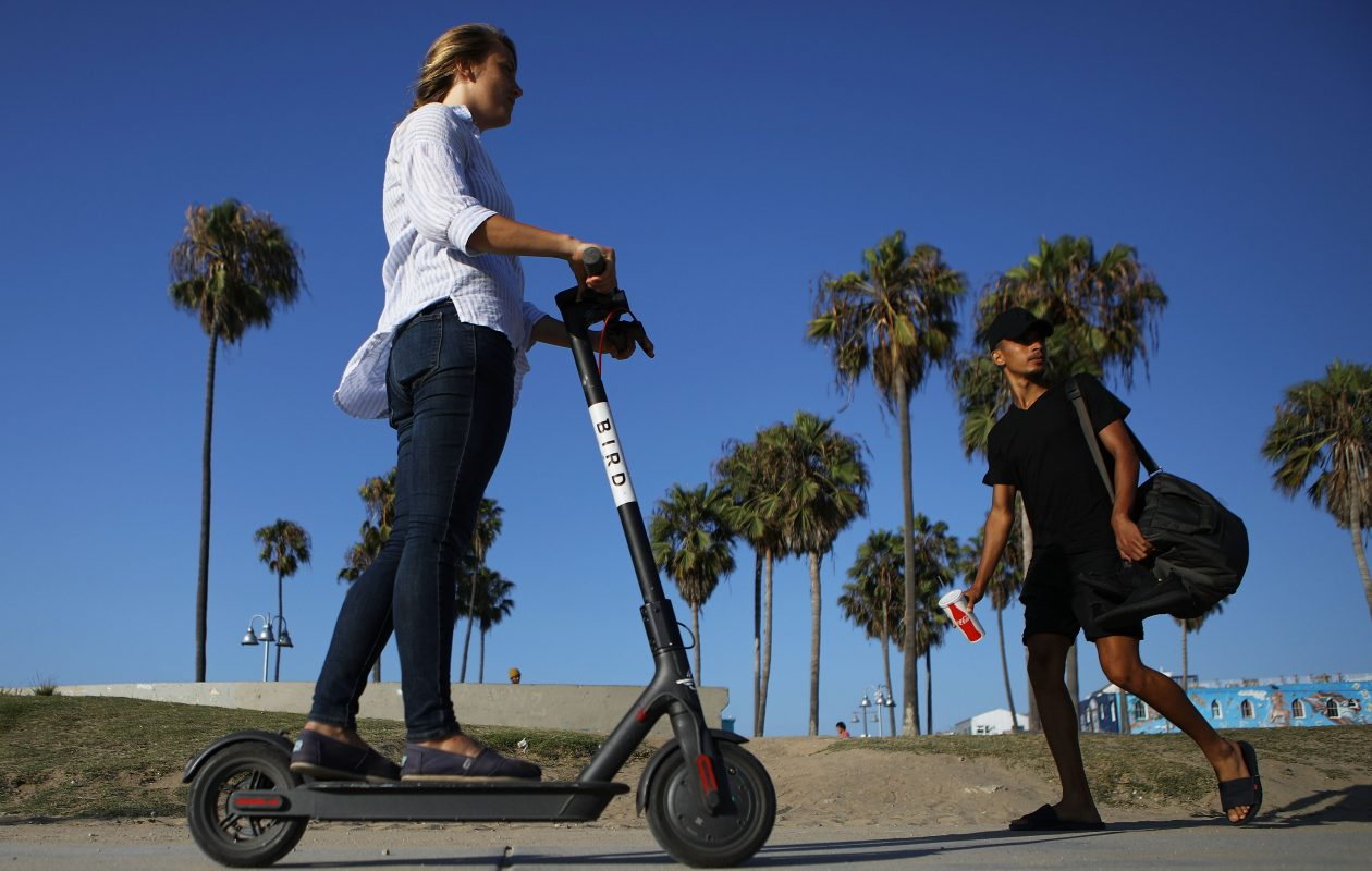 A woman rides a Bird shared dockless electric scooter along Venice Beach in Los Angeles, Calif. (Getty Images)