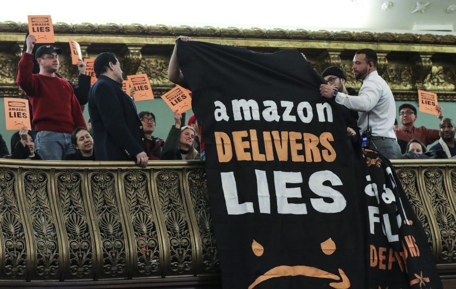 "Protestors unfurl anti-Amazon banners from the balcony of a hearing room during a New York City Council Finance Committee hearing titled ""Amazon HQ2 Stage 2: Does the Amazon Deal Deliver for New York City Residents?"" at New York City Hall on Jan. 30.  (Getty Images)"