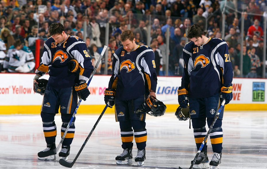 From left, Craig Rivet, Derek Roy and Drew Stafford of the Sabres pause for a moment of silence for the victims of Flight 3407 prior to playing the Sharks on Feb. 13, 2009. (Getty Images)