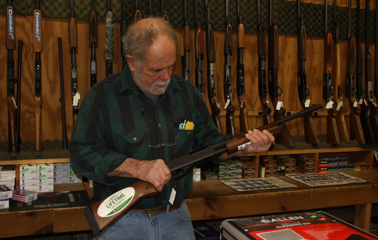 Al Johnson of Johnson's Country Store in Lockport shows off a Remington shotgun, a popular item in gun raffles. Under a new proposal, gun raffles could be a thing of the past. (Photo courtesy of Bill Hilts Jr.)