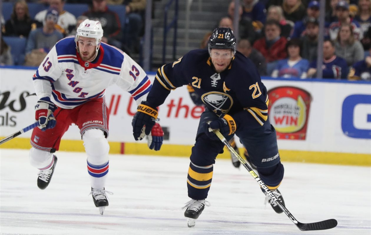 Kyle Okposo carries the puck ahead of New York's Kevin Hayes in the first period Friday night. (James P. McCoy/Buffalo News)