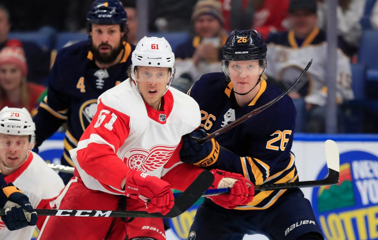 Rasmus Dahlin keeps the path clear in front of the net against Detroit's Jacob De La Rose. (Harry Scull Jr./Buffalo News)
