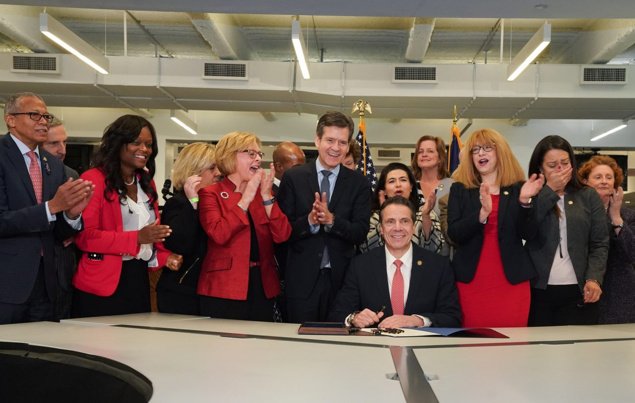 With bill sponsors Sen. Brad Hoylman, at his left, and Assemblywoman Linda Rosenthal on his right, Gov. Andrew Cuomo signs the Child Victims Act in the newsroom of the New York Daily News Thursday. 'It was the Daily News that told the story, that publicized the abuse, victims that came forward. It was the Daily News that started the drumbeat for justice....,' he said. (Photo provided by Gov. Cuomo's office)