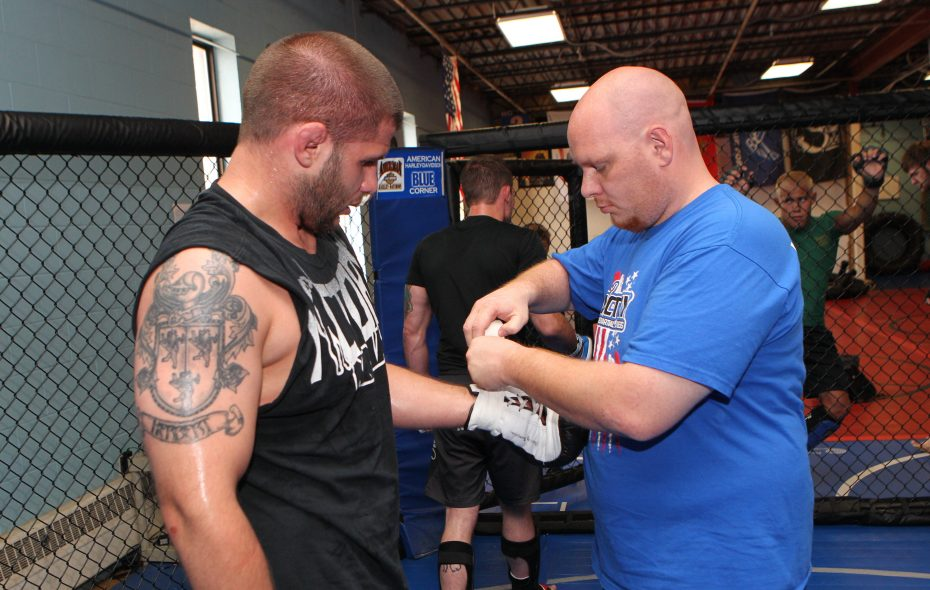 "In this 2012 file photo, Erik ""The Bull"" Herbert, left, has his gloves tied up by Don Lilly, right, the co-owner, trainer and manager at Victory Mixed Martial Arts & Fitness. Herbert is now a North Tonawanda policeman and Niagara County Legislature candidate. (Sharon Cantillon/News file photo)"