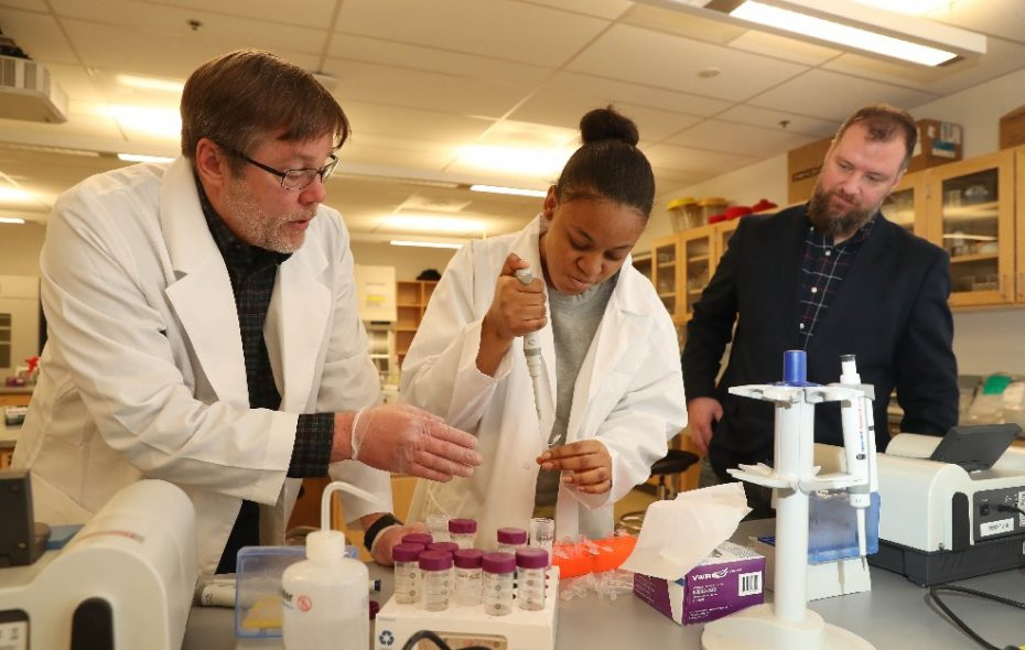 International Preparatory School ninth-grader Sole Witt learns to use a pipette to transfer material as part of a project to send bacterial specimens to outer space. Providing guidance are faculty adviser and SUNY Buffalo State Assistant Professor Derek Beahm, left, and I-Prep teacher and project adviser Andrew Franz. (Sharon Cantillon/Buffalo News)