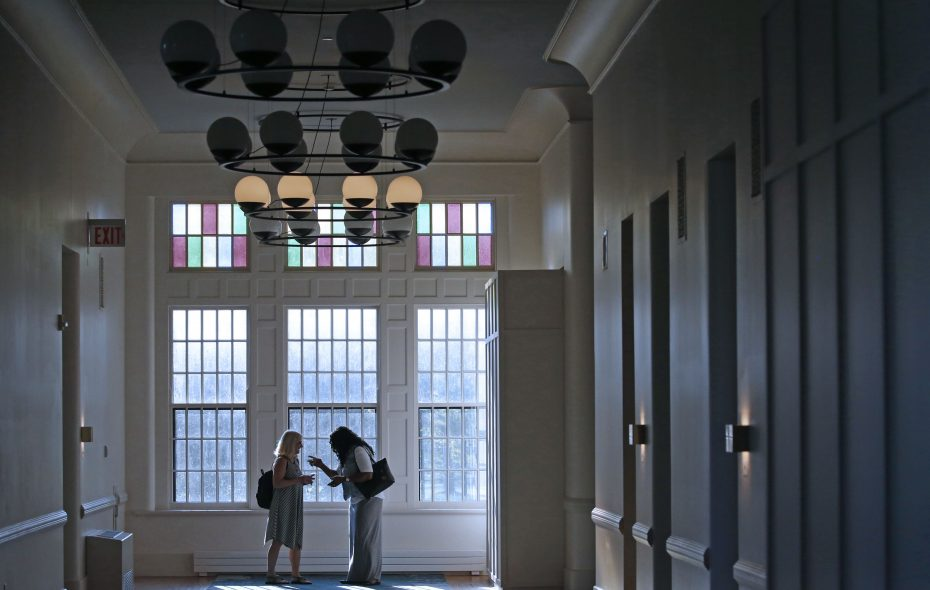 Guests talk at the end of a hallway on the second floor of Hotel Henry, one of several new entries in the competitive wedding venue business. (Robert Kirkham/Buffalo News)