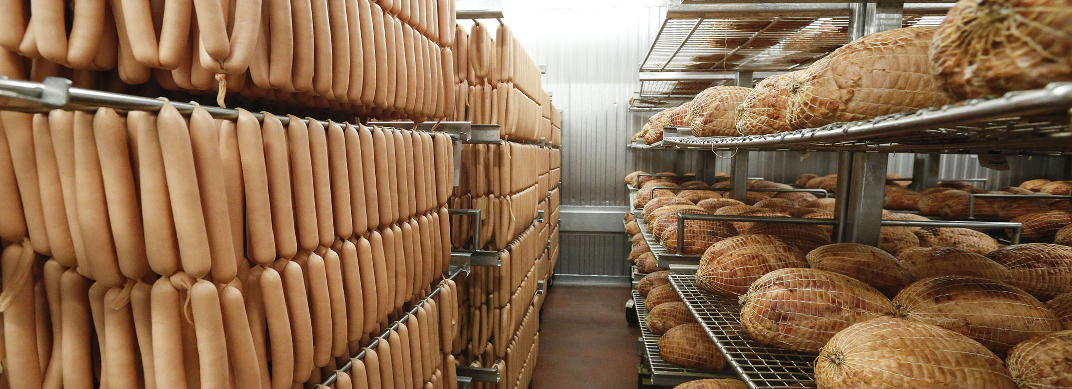 Racks of Sahlen's signature smokehouse hot dogs, left, and smoked hams are lined up in the packaging area at the Sahlen Packing Co, which has operated on Howard Street in Buffalo since 1869. (Derek Gee/Buffalo News)