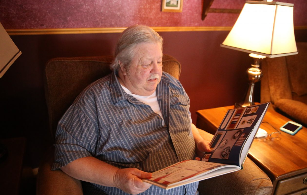 Vietnam veteran Mark Phillips looks at a book his daughter made with photos and awards he received from his days as a U.S. Army serviceman. (John Hickey/Buffalo News)