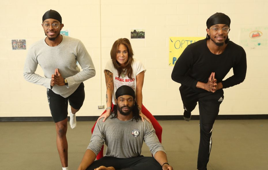 """Casey Sampson, left, and his brother, Cory, flank Baptiste yoga instructor Cheryl Erbacher and David """"Simba"""" Wedderburn. Erbacher helped the young men secure scholarships from Yogis in Service to take yogi certification classes. (Sharon Cantillon/Buffalo News)"""