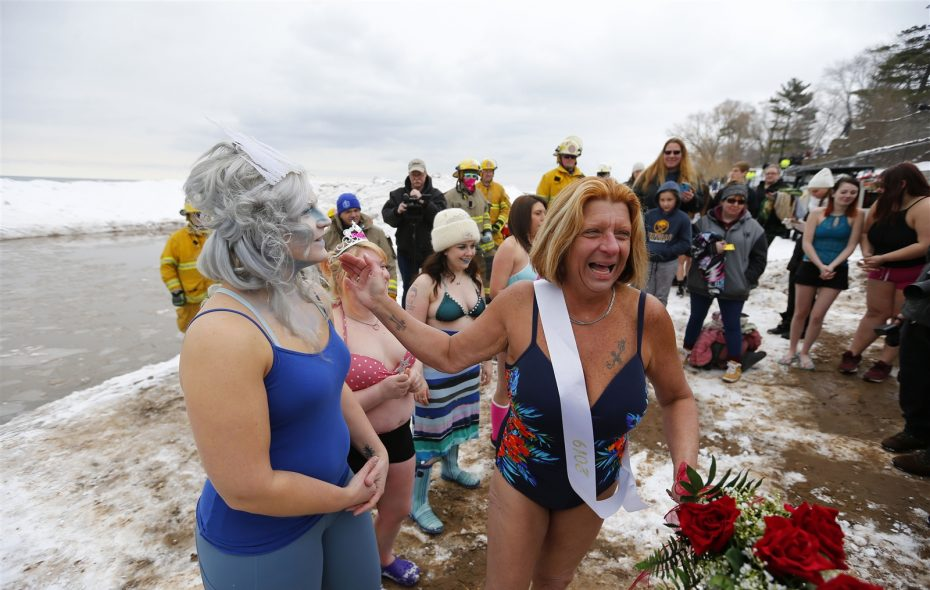 Competitors shiver after emerging from the icy water of Lake Ontario Sunday during the 50th annual Polar Bear Swim for Sight. (Mark Mulville/Buffalo News)