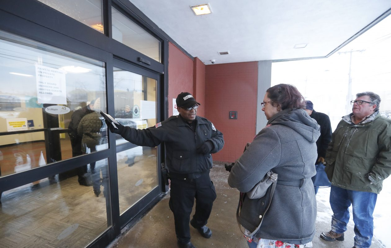 A security guard outside the CAO board meeting on Monday points out a 'private meeting' sign to former board member Jennifer Shank. The secret meeting adds to suspicions about what the CAO is hiding. (Mark Mulville/Buffalo News)