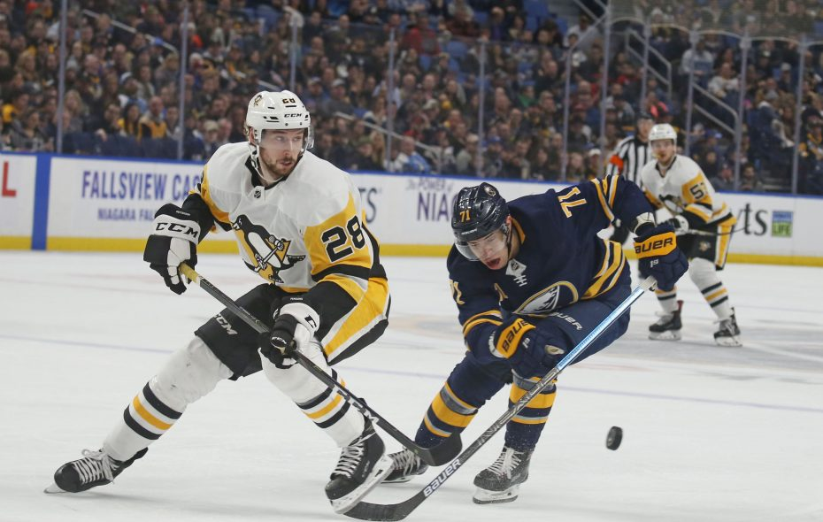 Buffalo's Evan Rodrigues and Pittsburgh's Marcus Pettersson both try to come up with a frantic puck. (Robert Kirkham/Buffalo News)