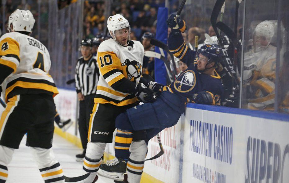 Pittsburgh's Garrett Wilson sends Buffalo's Johan Larsson into the bench in the first period. The Buffalo Sabres hosted the Pittsburgh Penguins at KeyBank Center in Buffalo on Thursday, March 14, 2019.  (Robert Kirkham/Buffalo News)