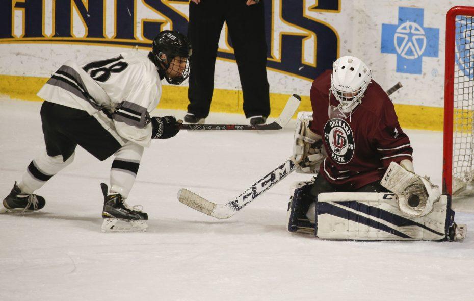Orchard Park goalie Ryan Albert makes a save against Syracuse's Skariwate Papineau. (Derek Gee/Buffalo News)