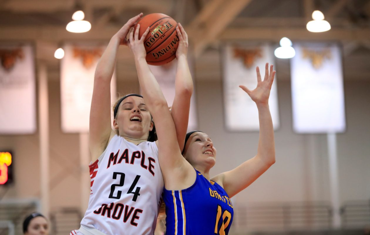 Maple Grove player Sam Snow and Oakfield-Alabama's Lizzy Tool battle for a rebound during the second half of the Far West Regionals Class C Championship at Buffalo State Sports Arena on Saturday, March 9, 2019. (Harry Scull Jr./Buffalo News)