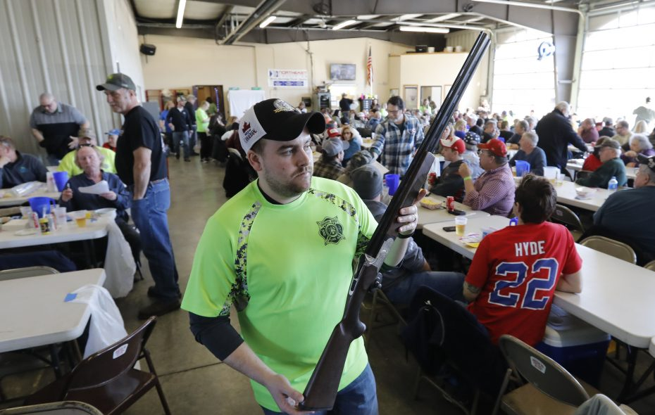 Firefighter Bryan Bader displays a Mossberg shotgun up for raffle during a gun raffle at the Jamison Road Volunteer Fire Company in Elma on Saturday. (Derek Gee/Buffalo News)