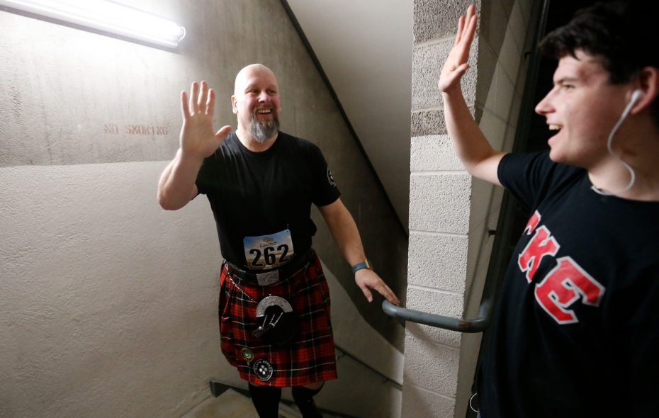 John Katalinas gets a high-five from a volunteer as he arrives at the finish line on the 24th floor Saturday during the Fight For Air Climb at Main Place Tower. (Derek Gee/Buffalo News)