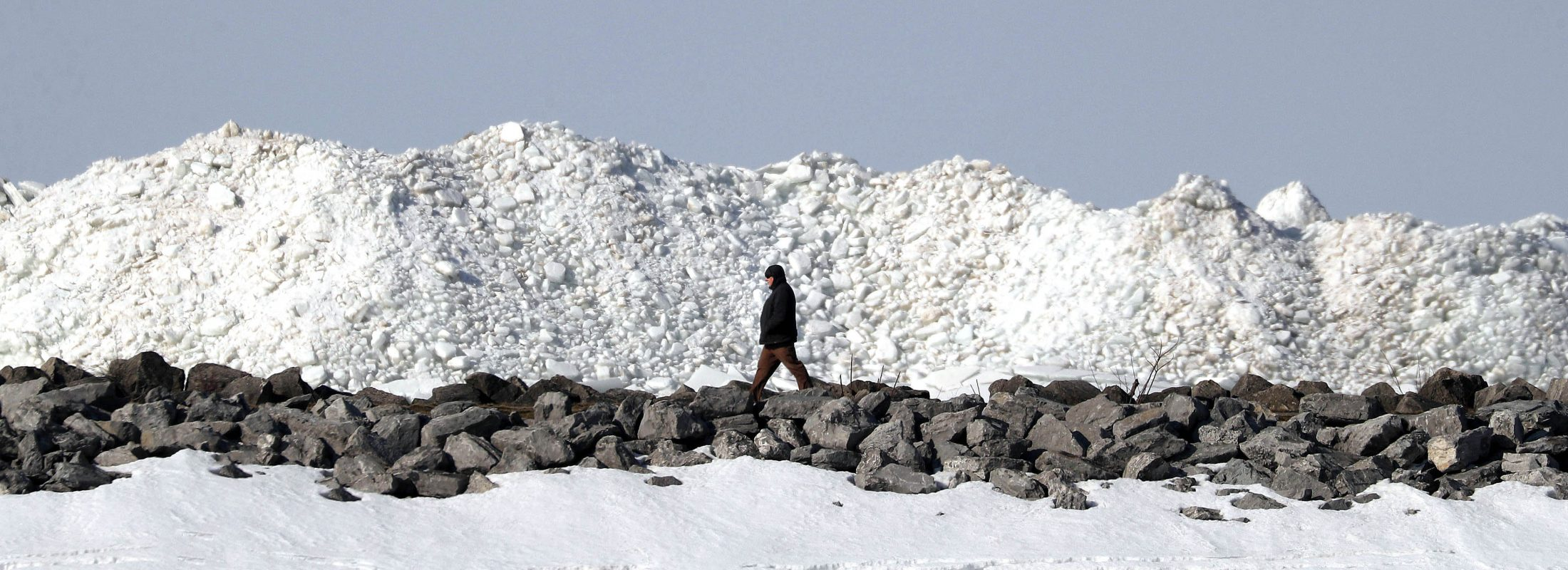 A pedestrian passes ice mounds while walking on the stone path at the small boat harbor in Buffalo on March 19. (Mark Mulville/Buffalo News)