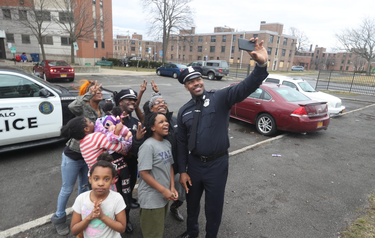 Buffalo police officers Armonde 'Moe' Bader, left, and Michael Norwood Jr. take a photo with residents of Commodore Perry housing complex after a video went viral earlier this year when they were caught on video singing an Ed Sheeran song at the Salsarita's downtown. (John Hickey/Buffalo News)