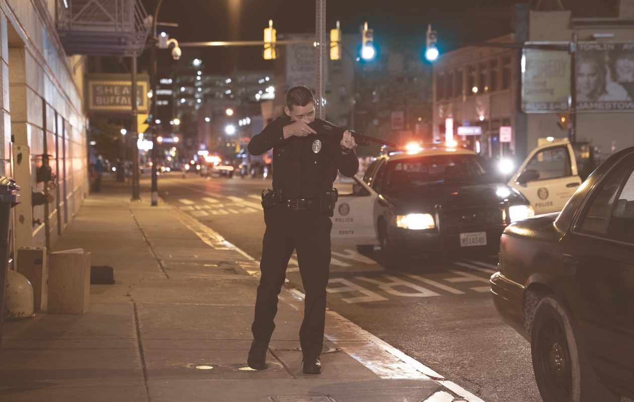 Shea's Buffalo Theatre is seen in the background of this scene from the feature film 'Crown Vic.' Pictured is  Luke Kleintank, starring as rookie police offer Nick Holland. (Photo by Phil Caruso)