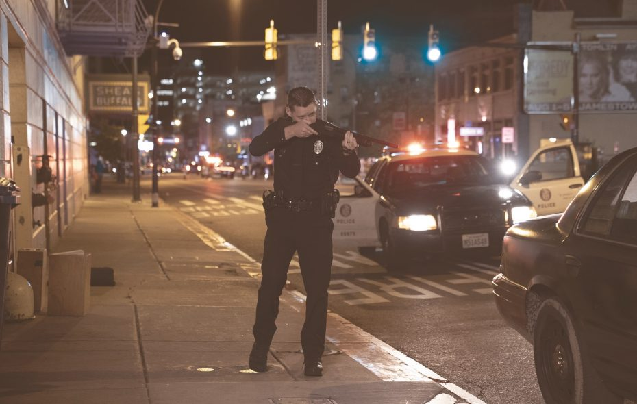 "Shea's Buffalo Theatre is seen in the background of this scene from the feature film ""Crown Vic."" Pictured is  Luke Kleintank, starring as rookie police offer Nick Holland. (Photo by Phil Caruso)"