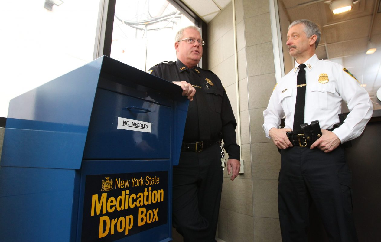 Michael Neithe, then a Lockport police captain, left, and then-Chief Lawrence Eggert, right, stand next to the drop box for unwanted prescriptions that remains in the department's headquarters. (Mark Mulville/News file photo)