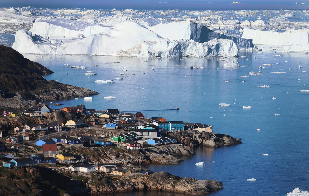 A July 2013 photo shows  the village of Ilulissat, Greenland,  near icebergs that broke off from the Jakobshavn Glacier.   What had been the fastest thinning large Greenland glacier has significantly slowed its loss of mass. Colder ocean currents were found to be the cause. (Getty Images)