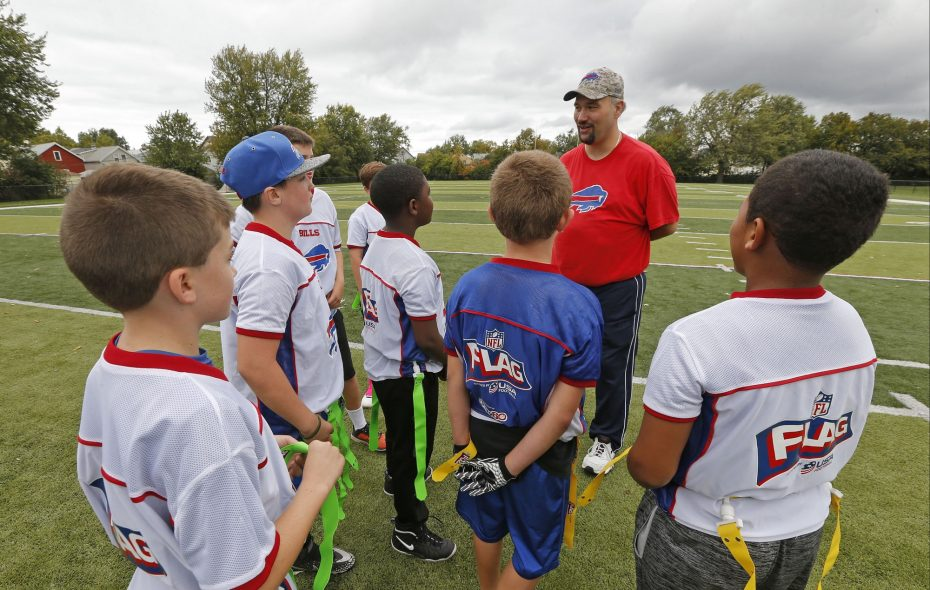 Youth Advantage League Commissioner Christopher A. Denny addresses some of the members of a boys flag football program practice at Pierce Field in Mulroy Park, South Buffalo. The program bubbled up from the Healthier Districts Initiative designed to help address low health rankings in the region.  (Robert Kirkham/News file photo)