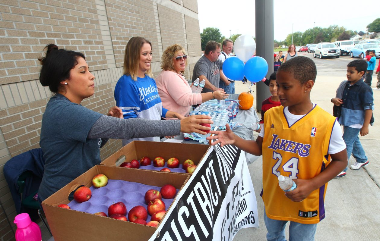 Anna Rodriguez, left, hands an apple to Kobe Underwood, who did three laps around the Martin Road Elementary School in Lackawanna in 2017 as part of the Healthiest District Initiative. (John Hickey/News file photo)