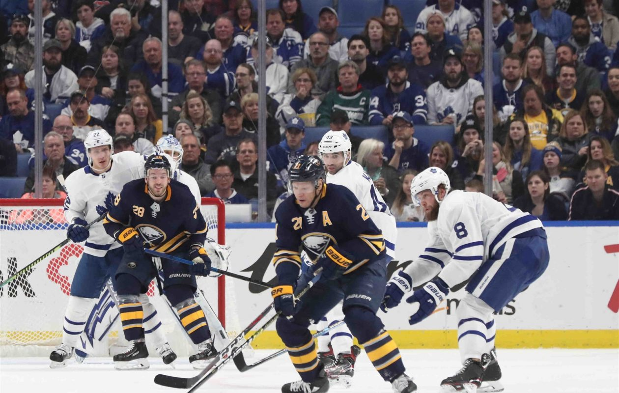 Kyle Okposo works the puck in the Leafs' zone against defenseman Jake Muzzin (8) as Zemgus Girgensons (28) sets a screen in front of the net Wednesday night (James P. McCoy/Buffalo News).
