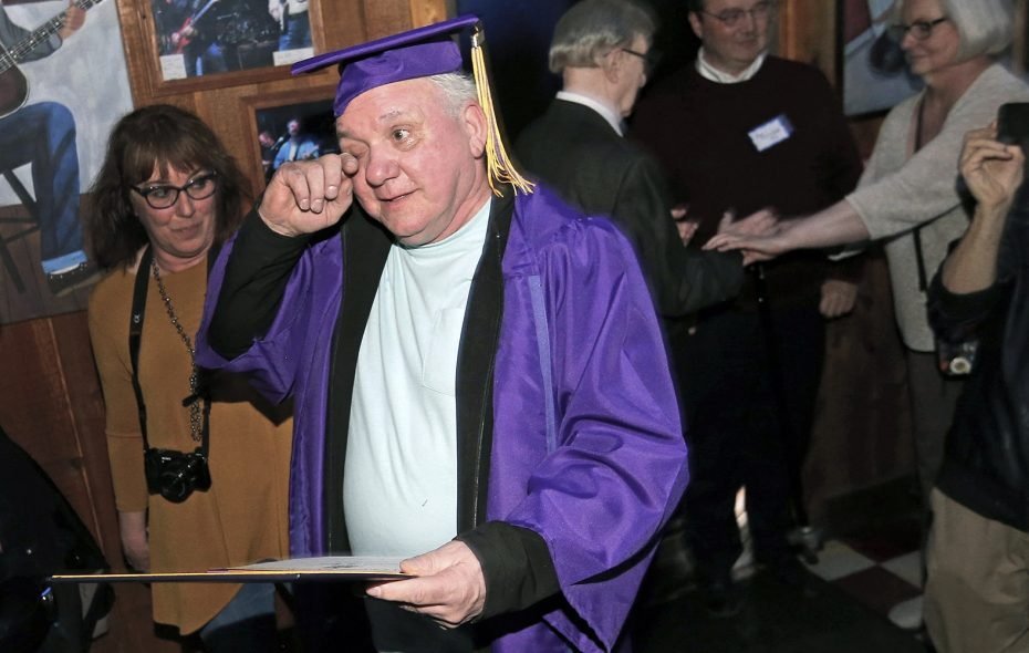 Dwane Hall wipes away a tear while holding his new high school diploma March 28. (Robert Kirkham/Buffalo News)
