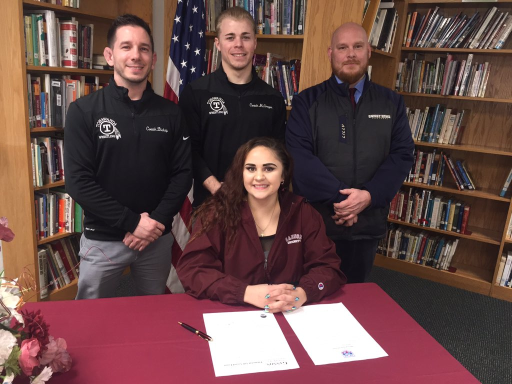 Tonawanda coach Dan Bishop (from left), Tonawanda assistant coach Jordan McGregor and Sweet Home coach Don Lilly flank Bailey Crouse after she signed her letter of intent to wrestle at Gannon. (Photo courtesy of the Crouse family)